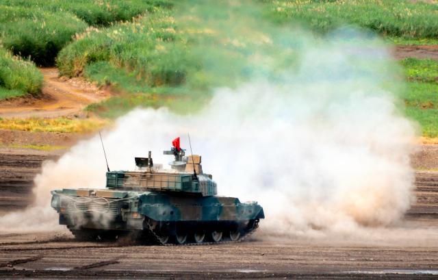 陸上自衛隊で最新式の戦車「10式」。この「後退蛇行射撃」は場内アナウンスで「高い射撃性能と機動性で実現した非常に難易度の高い射撃」と説明された=8月27日午前11時すぎ、静岡県の陸自東富士演習場