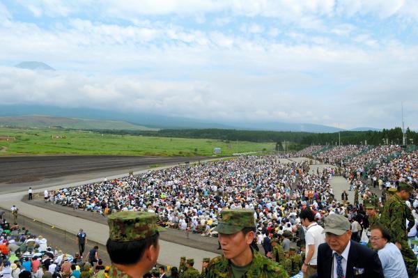 昼間演習を前に満員の観客席。29倍超の抽選でチケットを手にした人から、招待された自衛隊や在日米軍などの関係者ら約2万4千人が詰めかけた=8月27日午前、静岡県の陸自東富士演習場