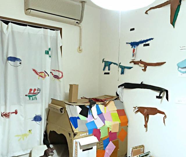佐藤さんの自宅。右の壁にはキャプションつきの作品たち。真ん中の段ボールの家も息子さんの手作りで、カーテンはおもちゃ作家である奥様が息子さんの絵をプリントしたとのこと。