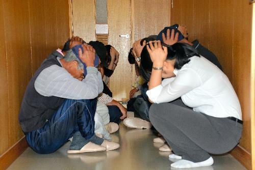 訓練で窓のない廊下に避難し、かがんで頭を守る地域住民ら=青森県つがる市