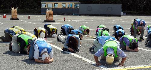 弾道ミサイルの発射を想定した訓練で地面に伏せる参加者=千葉市緑区