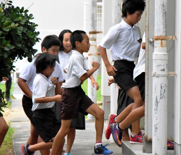 愛媛県西条市でのミサイル避難訓練で体育館へ駆け込む小学生ら=7月10日