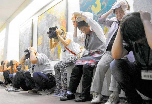 石川県輪島市でのミサイル避難訓練で、建物に逃げ込み身をかがめて頭を守る人たち=8月30日