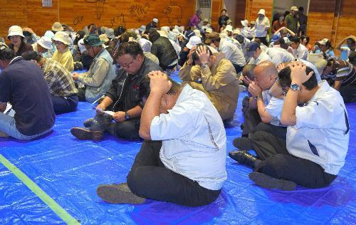 訓練で体育館に避難し、頭を手で覆うなどする住民ら=北海道滝川市
