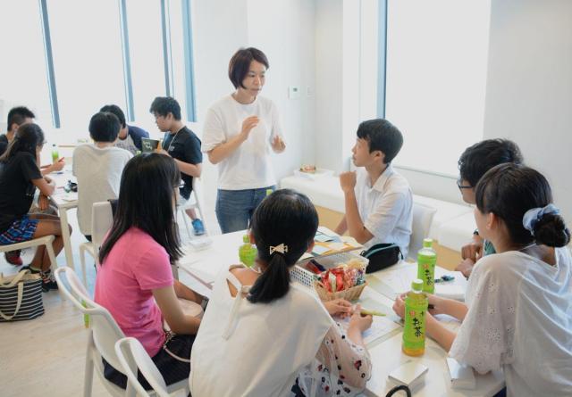 白いTシャツとジーパンのカジュアルなスタイルで高校生と語らう岡島礼奈さん