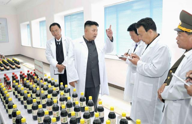 北朝鮮の平壌にある食品工場を視察する金正恩氏。黒い液体の入ったびんのラベルには「鶏肉風味のしょうゆ」と書かれているとのこと。朝鮮中央通信が配信した(本文とは関係ありません)=2013年6月8日