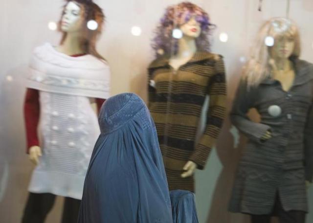 アフガニスタンのへラートでショーウィンドウの婦人服を眺めるブルカをまとった女性=ロイター