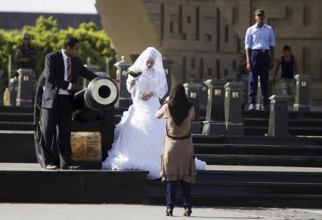 エジプトのサダト大統領の墓地で記念写真を撮る新郎新婦=ロイター