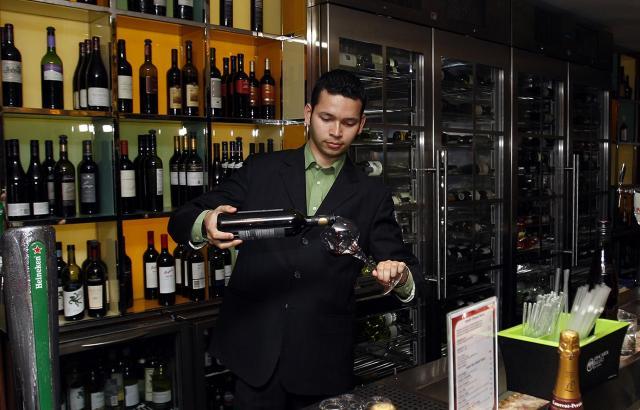 ドバイのバーで、アルコールをグラスに注ぐバーテンダー=2011年7月1日