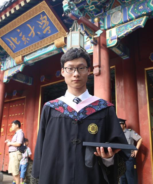 北京大から東大に留学した呉さん。北京大の西の門を背景にした卒業式の写真