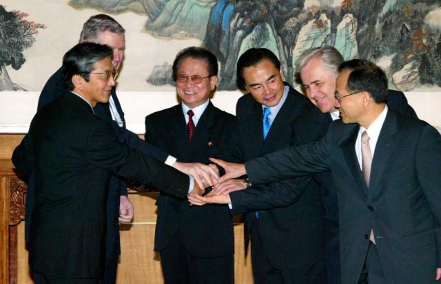 2003年8月、北朝鮮の核問題をめぐり、中国、北朝鮮、韓国、米国、日本、ロシアで始まった6者協議が初めて開かれ、6カ国の代表(当時)が協議を前に握手を交わした=北京市の釣魚台、江口和裕撮影