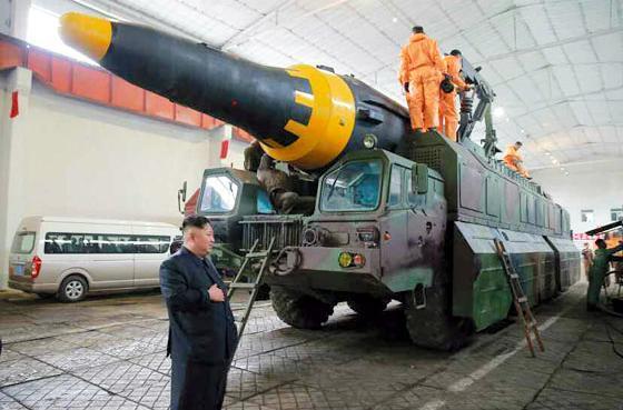 移動発射台に搭載された新型ミサイルを視察する金正恩委員長(手前)=2017年5月15日付の労働新聞(電子版)から