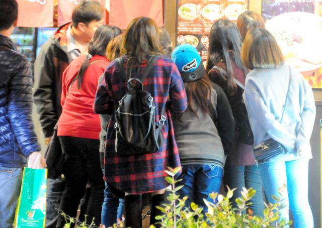 豚骨ラーメン店の前に行列をつくる外国人観光客たち。順番を待つ間、メニューに見入っていた=2015年12月18日、那覇市