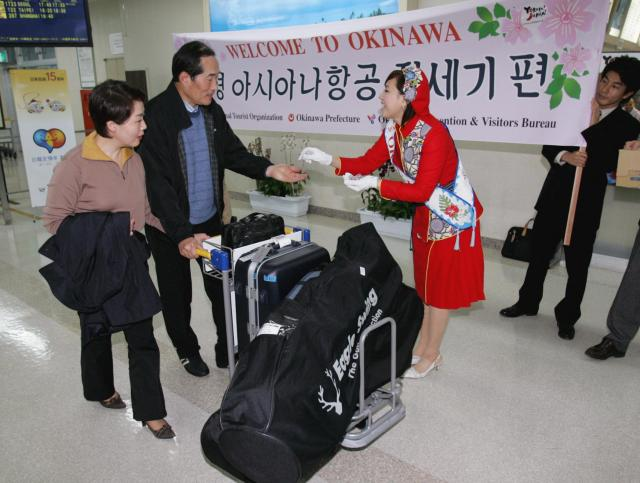 チャーター便で到着の韓国人ゴルフ客を出迎える「ミス沖縄」が=2005年2月4日、那覇空港で