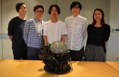 AI-CD β(手前中央)と、島村譲さん(奥中央)、吉富亮介さん(同右から2人目)らプロジェクトの仕掛け人たち。5人全員が20、30代=東京都港区