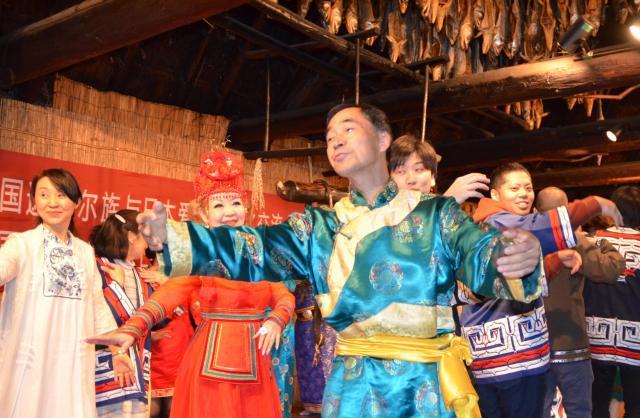 民族衣装でアイヌ民族博物館の職員と一緒に踊る中国ダフール族のメンバーら=2017年5月23日、白老町、深沢博撮影