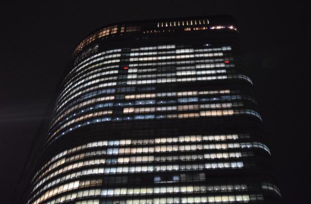 夜9時台の電通本社ビル。多くの窓から明かりが漏れていた
