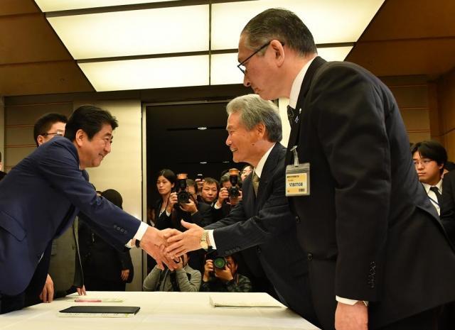会談を終え、経団連の榊原定征会長と握手する安倍晋三首相。右手前は、連合の神津里季生会長=3月13日、首相官邸