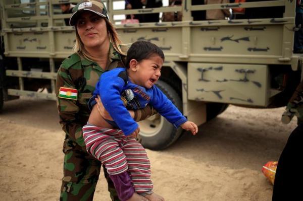 少年を抱きかかえる「ペシュメルガ」の女性兵士=2014年9月15日、ロイター