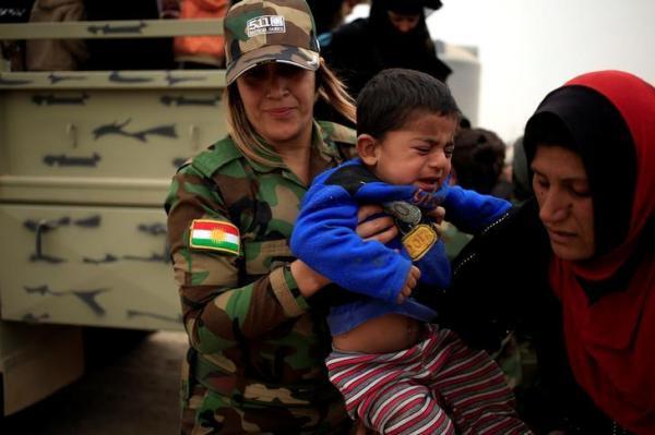 少年を抱ku「ペシュメルガ」の女性兵士=2014年9月15日、ロイター