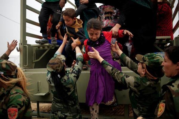 少女を助ける「ペシュメルガ」の女性兵士=2016年10月28日、ロイター