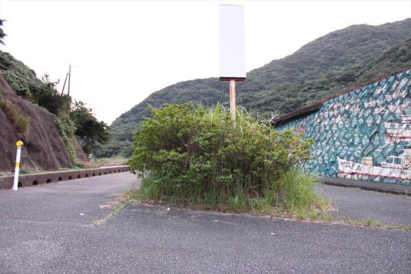 台風の後、植え込みの下に置かれていた「サバー送り」の人形はなくなっていた=2017年9月21日、山口県下関市豊北町
