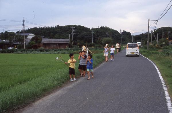 田んぼの中を運ぶ子たち=2002年7月19日、油谷町伊上浅井、山口県下関市立豊北歴史民俗資料館提供