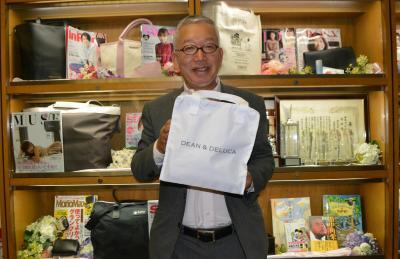 約50万部を売った「GLOW」2017年8月号の付録の保冷バッグを持つ関川誠さん=宝島社
