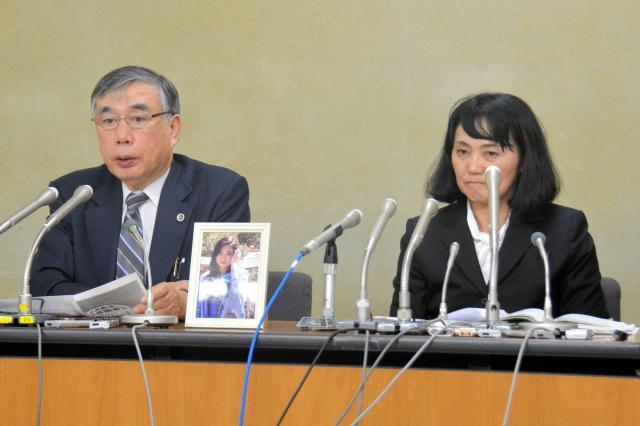 初公判の後、高橋まつりさんの遺影を持参し、会見する母幸美さん(右)と川人博弁護士=2017年9月22日、東京・霞が関の厚生労働省