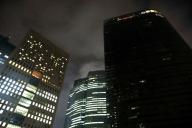 午後10時過ぎに電通本社ビル(右)は一斉に消灯された=2016年10月25日、東京都港区、林紗記撮影
