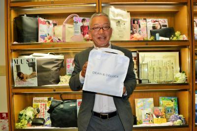 約50万部を売った「GLOW」8月号の付録の保冷バッグを持つ関川誠さん=宝島社
