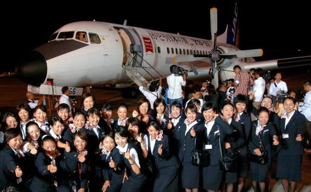 最後の運航を終えたYS11の前では客室乗務員たちが記念写真を撮った=2006年9月30日、鹿児島県霧島市の鹿児島空港で、長澤幹城撮影