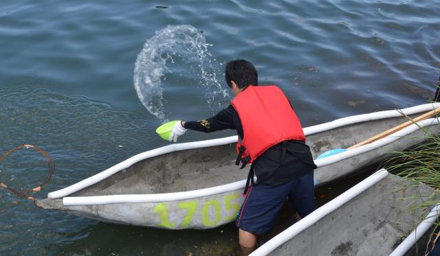 カヌー内に入ってきた水をかき出す場面も