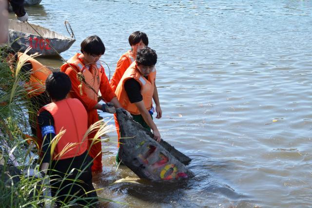 転覆したカヌーの引き揚げ作業。学生が力を合わせて引き揚げます