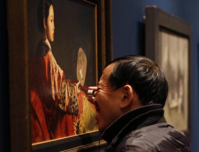 北京であったアートウィークのサザビーズのオークション会場で絵画を見る中国人男性=ロイター
