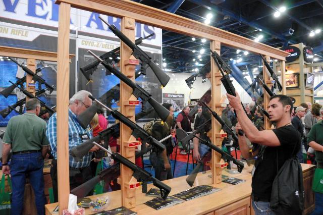 2013年のNRA年次総会で、展示された銃を手にとる参加者=2013年5月、アメリカ・テキサス州