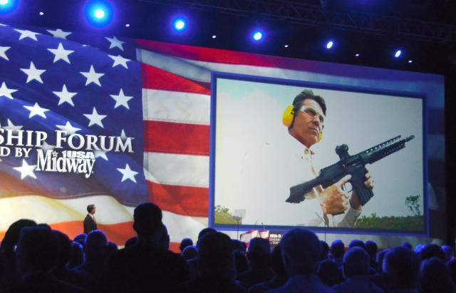 2013年のNRA年次総会では、テキサス州のリック・ペリー知事が、自らが銃を撃つビデオを上映してから登壇した=2013年5月、アメリカ・テキサス州