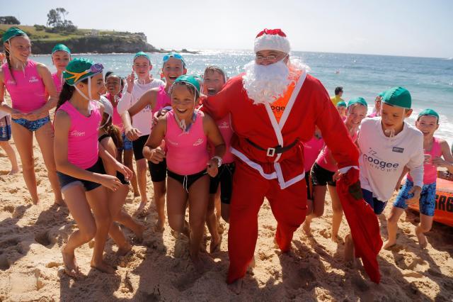 ビーチで子どもたちとふれあうサンタ。南半球のオーストラリアでは、12月は夏まっさかり=2016年12月11日