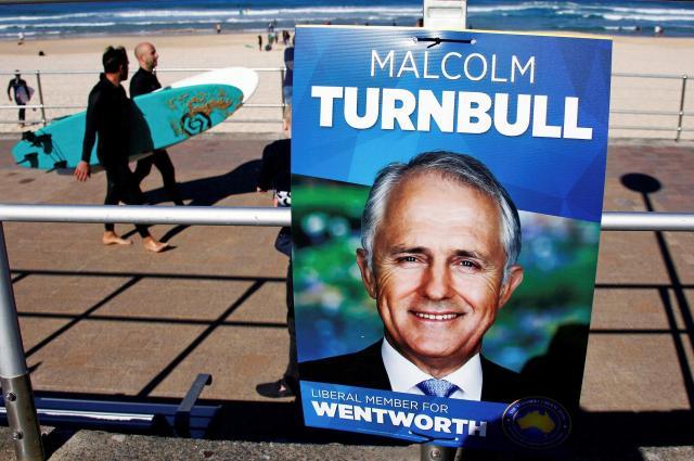 オーストラリアのシドニーで総選挙の投票日、ターンブル首相のポスター近くを歩くサーファーたち=2016年7月2日