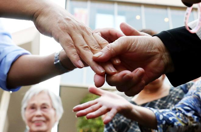演説を終えた候補者(左)に握手を求め、激励する有権者=2017年10月10日、東京都品川区、池田良撮影