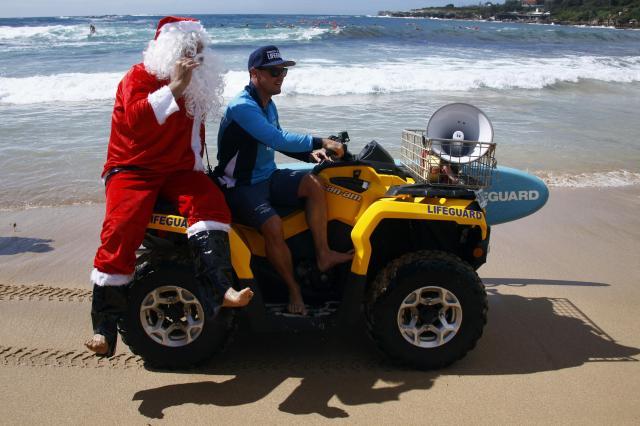 四輪車でビーチを疾走するサンタ=2014年12月14日