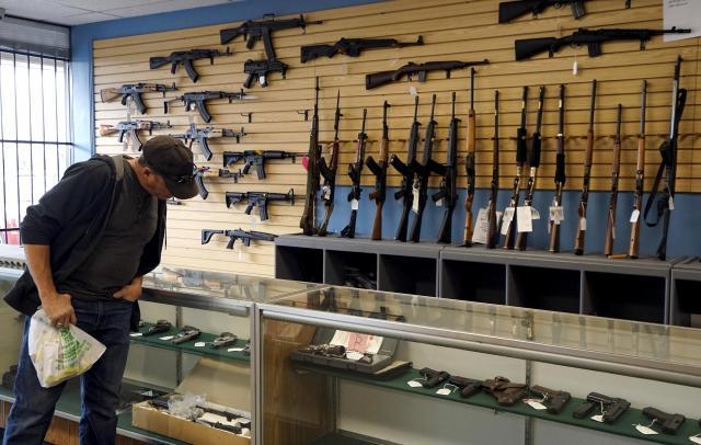 銃器店で、銃を見定める客=2015年12月、アメリカ・コロラド州