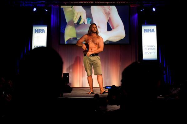 NRAが開いたファッションショーで、腰に携帯するホルスターに銃を入れるモデル=2017年8月、アメリカ・ウィスコンシン州