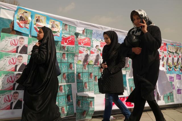 イランの首都テヘランで、選挙ポスターの貼られた掲示板の前を通り過ぎる人たち