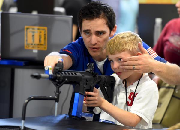 全米ライフル協会(NRA)の銃を展示するイベントで、子どもに銃を教える指導員=2015年4月、アメリカ・テネシー州