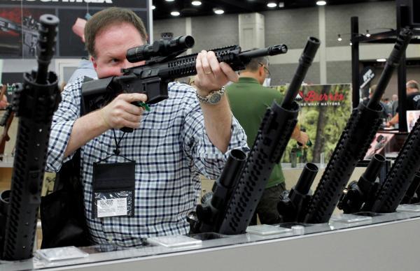 NRAの銃を展示するイベントで、ライフルのスコープをのぞき込む参加者=2016年6月、アメリカ・テネシー州