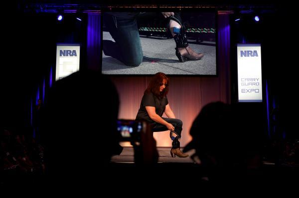 NRAが開いたファッションショーで、足に付けたホルスターの銃を見せるモデル=2017年8月、アメリカ・ウィスコンシン州