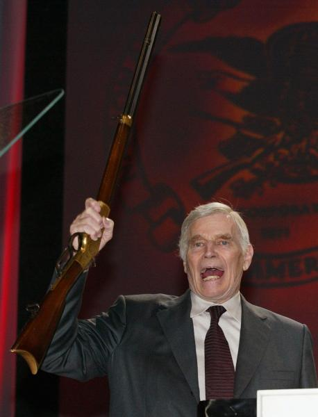 2003年のNRA年次総会で、ライフルを持って演説するチャールトン・ヘストン会長(当時)=2003年4月、アメリカ・フロリダ州
