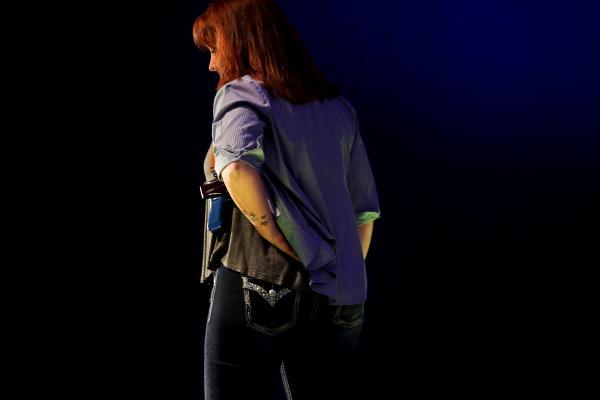 NRAが開いたファッションショーで、ホルスターに銃を入れるモデル。服の中で隠れているのが分かる=2017年8月、アメリカ・ウィスコンシン州