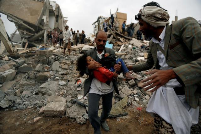 イエメンの首都サナアで、サウジ率いる連合軍の空爆でがれきと化した建物から、負傷した少女を運び出す男性=2017年8月25日